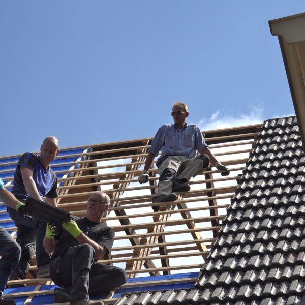 Fred, Wes,Sander en Hans leggen pannen op het onbeschoten dakdeel.