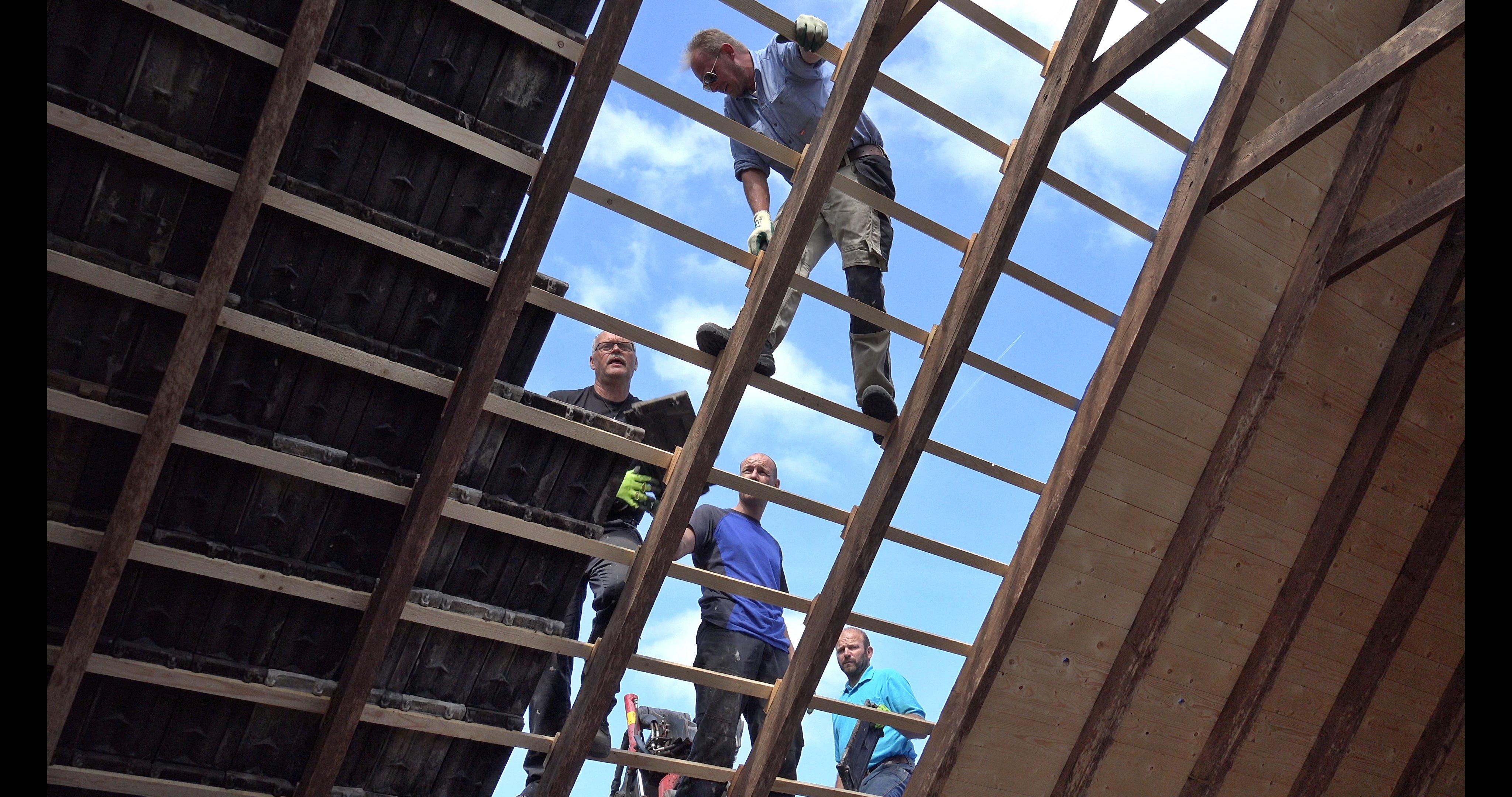 Fred, Wes,Sander en Hans leggen pannen op het onbeschoten dakdeel