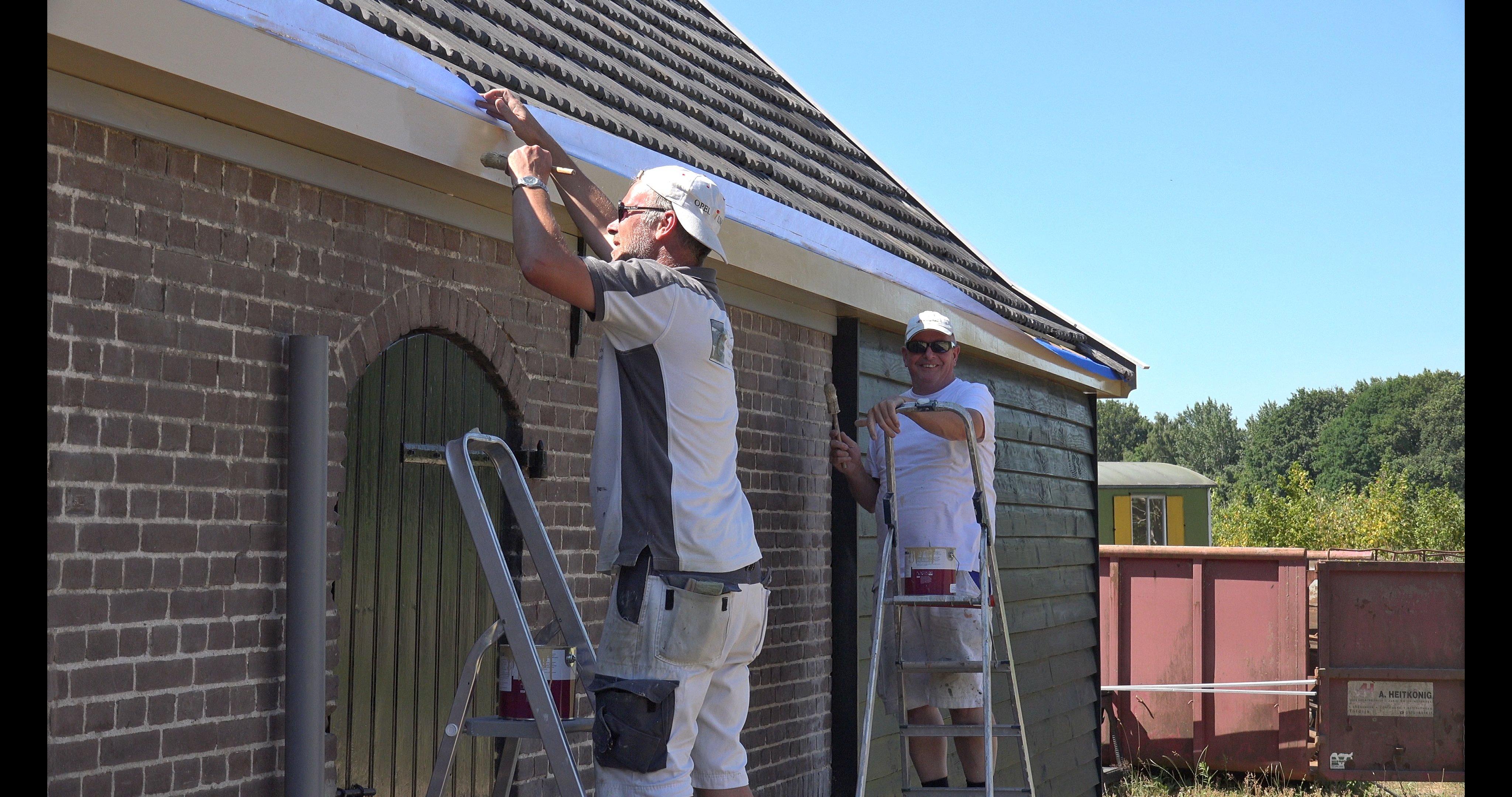 Erwin en Eric schilderen de daklijst.