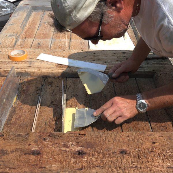 Erwin repareert een aangetaste staldeur van het achterhuis..