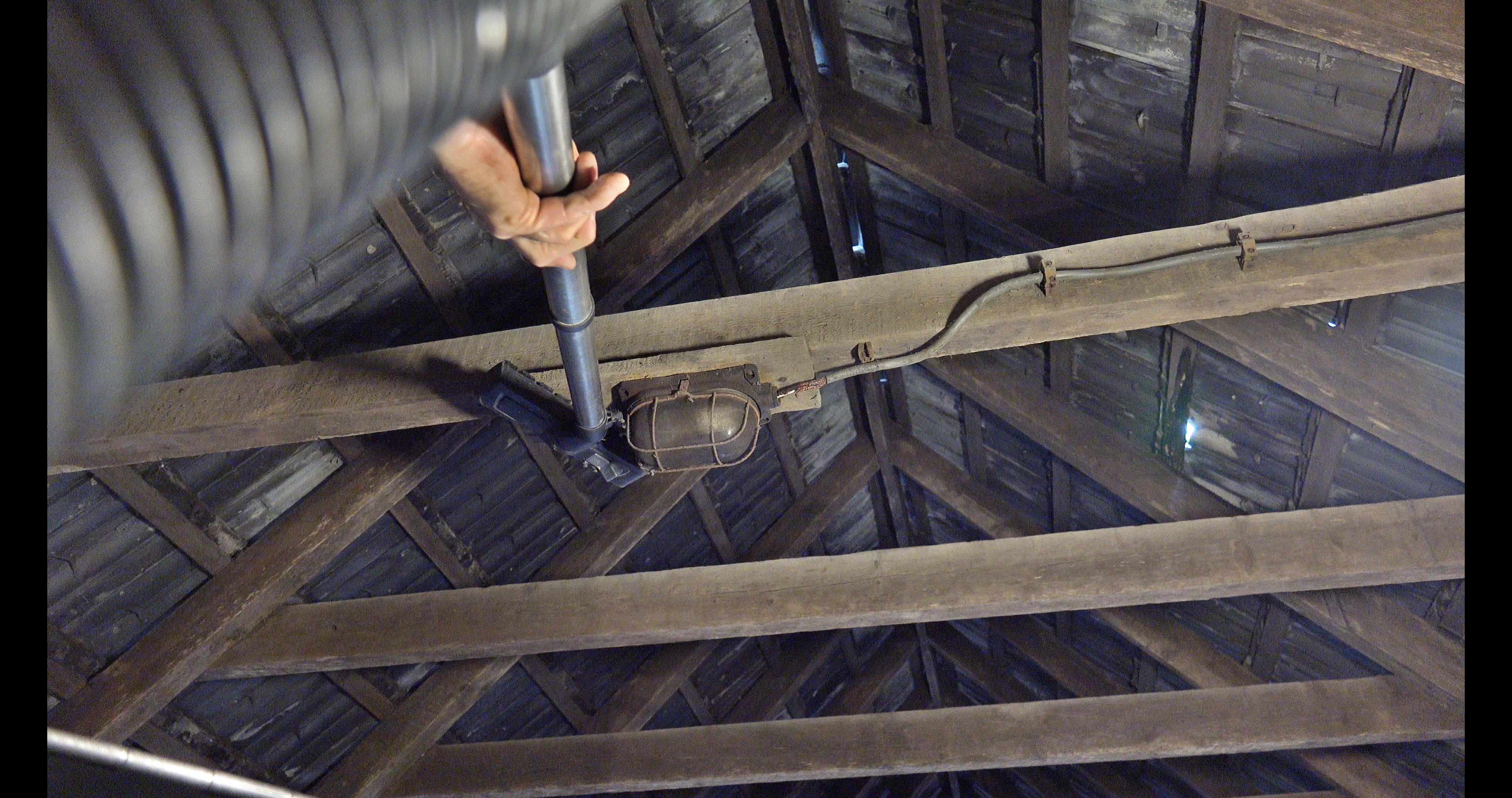 Han zuigt de hanenbalken schoon vanuit een hoogwerker.