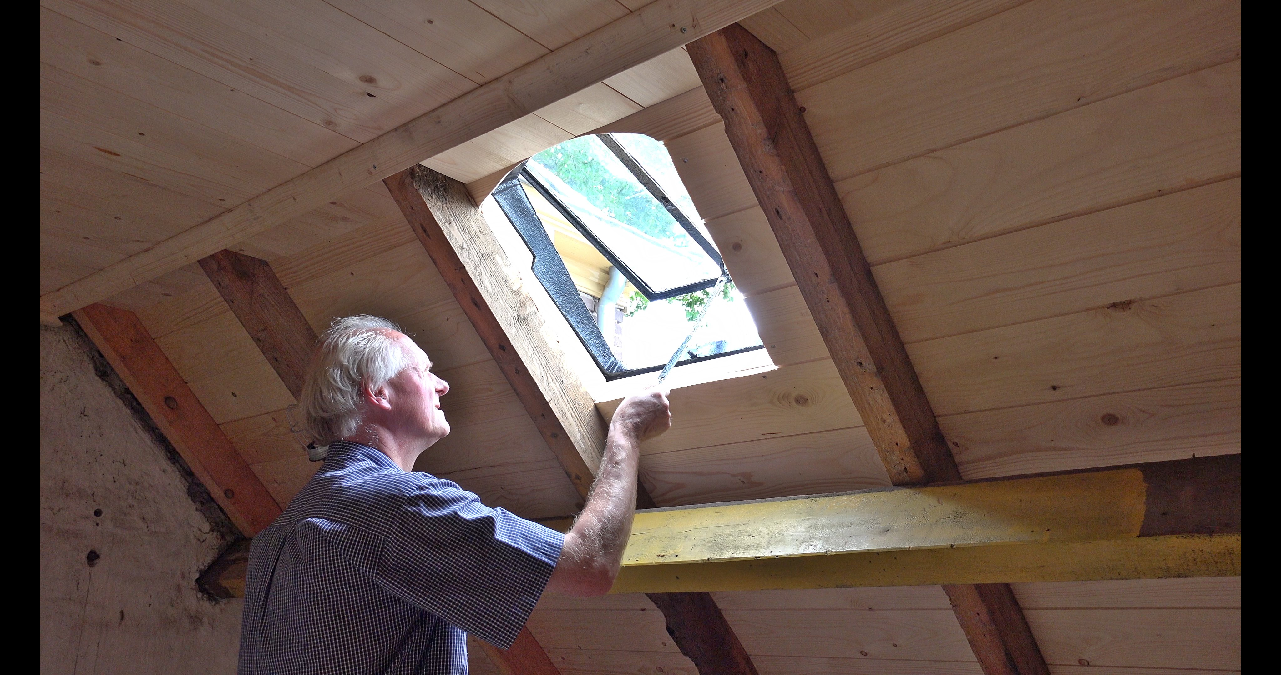 Han opent het dakraam in de knechtenkamer.