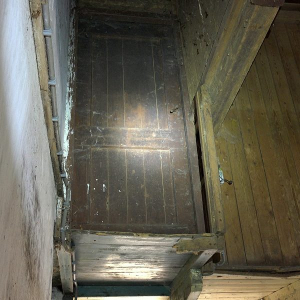 De deur van de knechtenkamer voor restauratie.