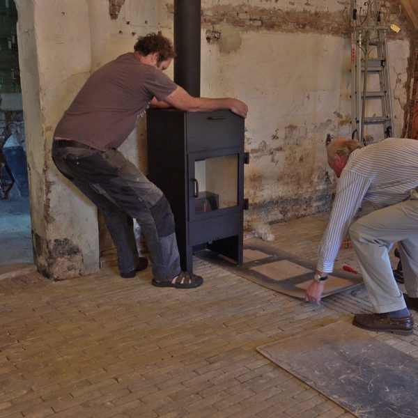 Peter plaatst de houtkachel in de schuur.