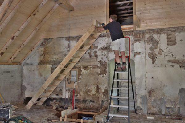 Peter monteert een trap in de schuur.