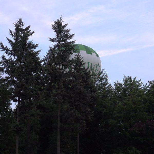 Een luchtballon scheert over het erf.