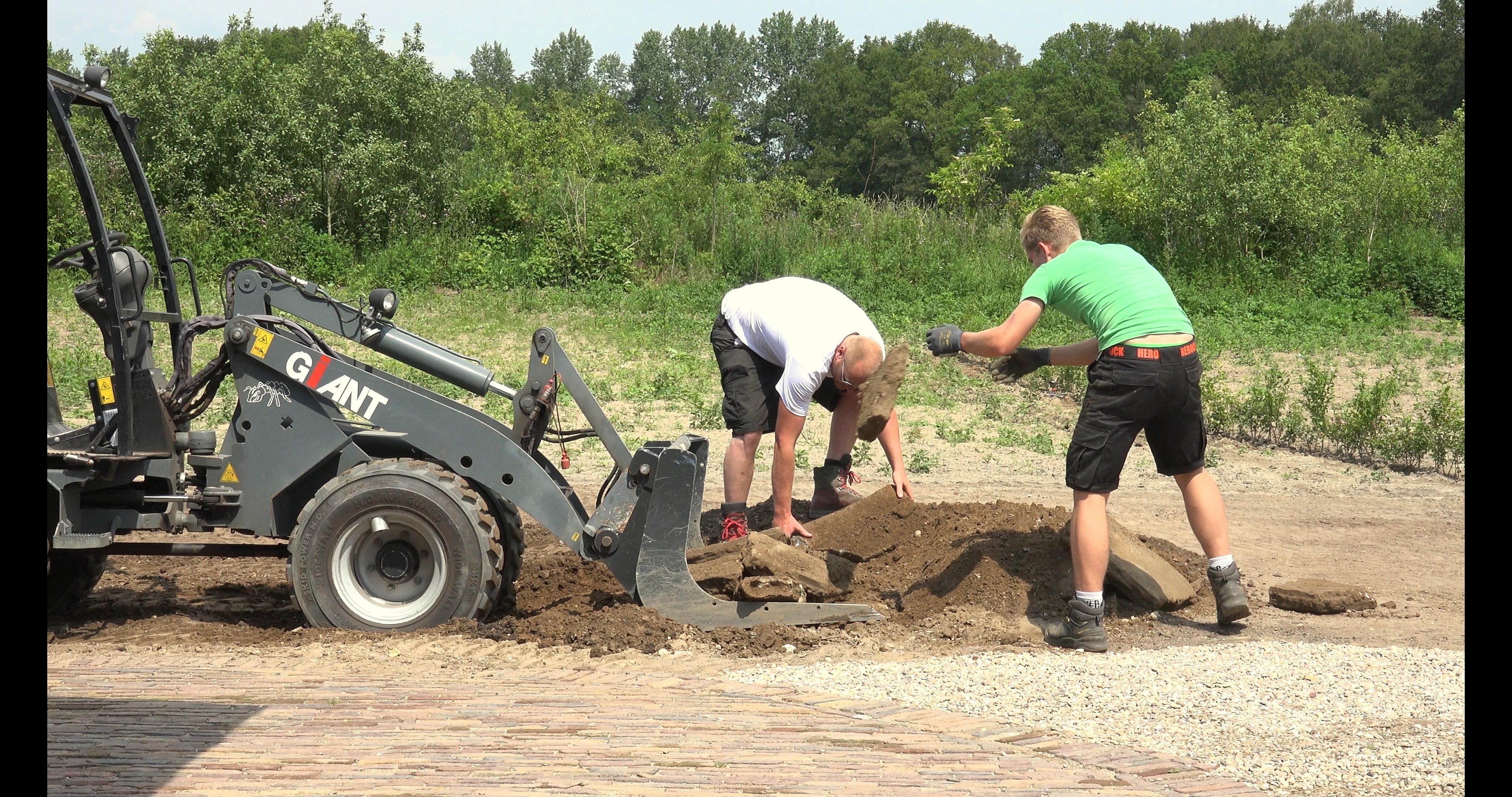 Sietse en Sem verwijderen puin op het erf achter.