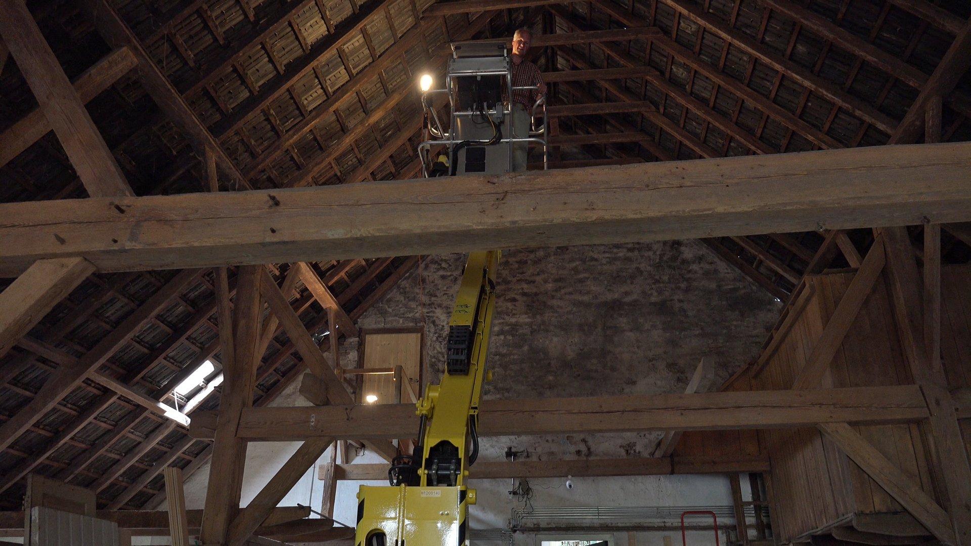 Han in de hoogwerker om het dak schoon te maken.