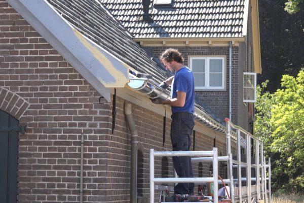 Mark monteert de dakgoten.
