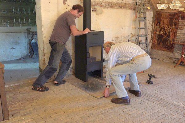 Peter en Han plaatsen de houtkachel.