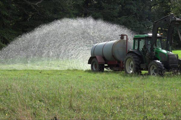 Het water uit de schuur wordt over het land gesproeid.