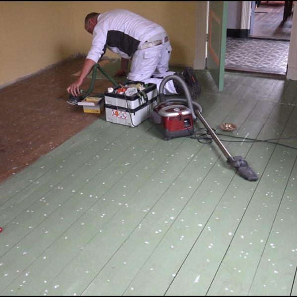 Erwin en Eric schilderen de eetkamervloer.