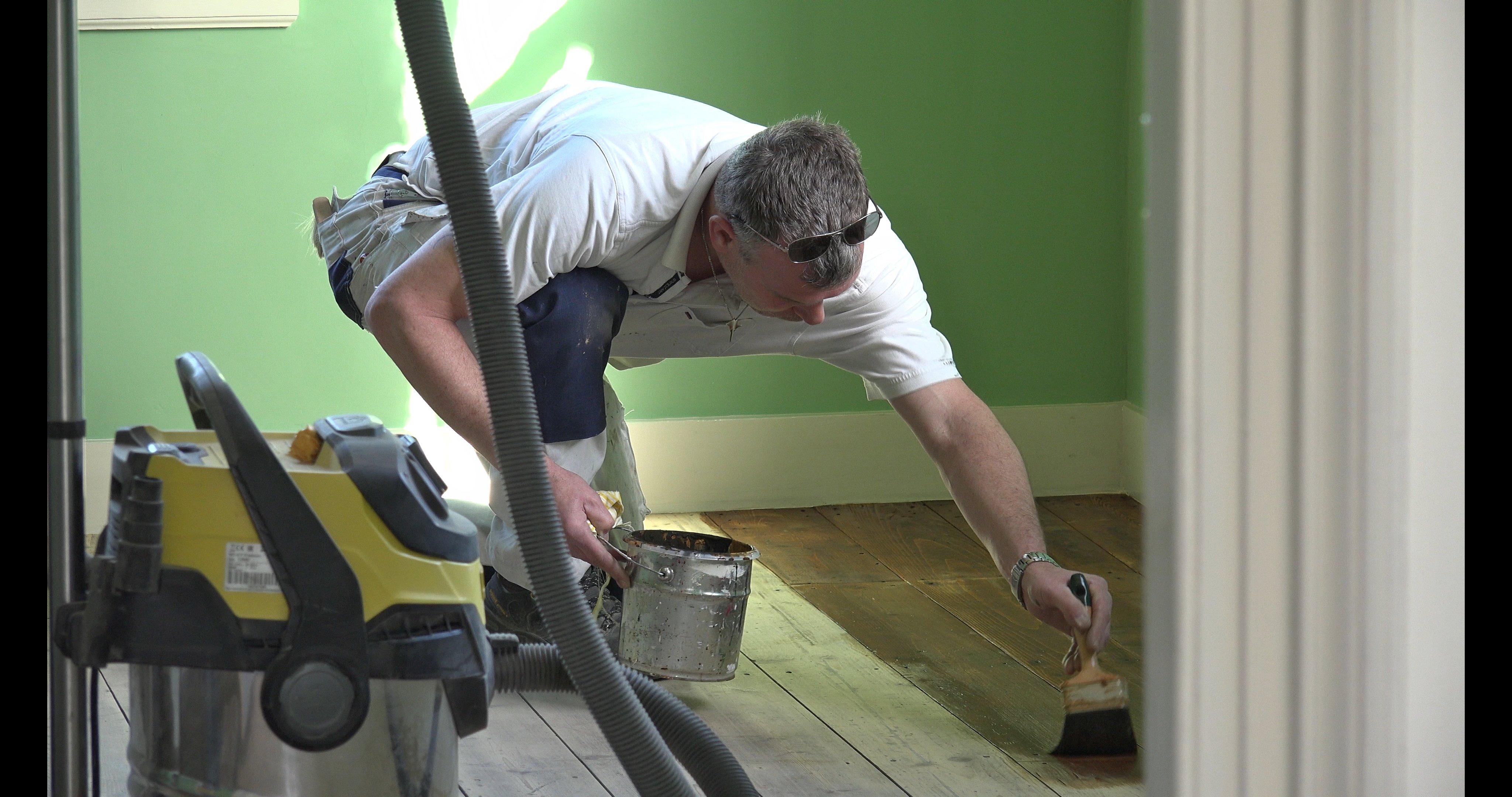 Erwin beitst de vloer van de zitkamer in middeneiken.