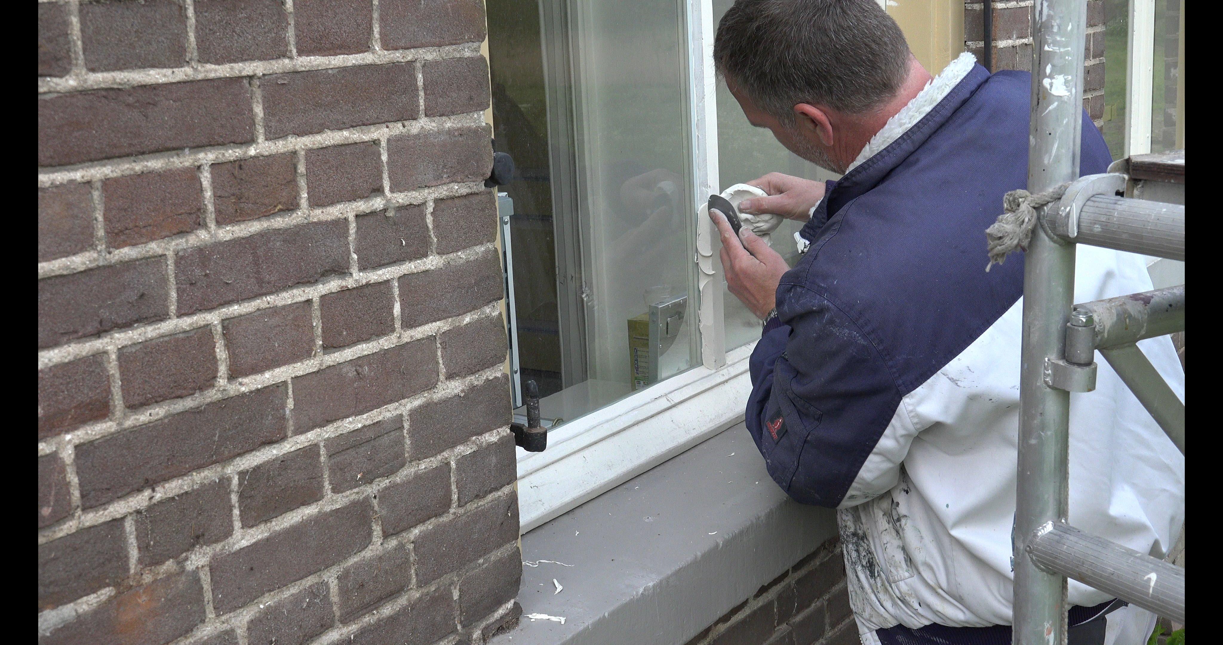 Erwin zet een raam in stopverf.