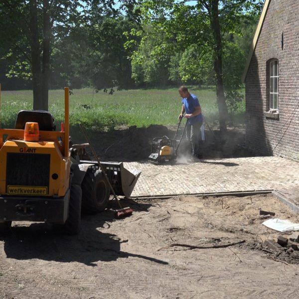 Robert en Kees leggen een terras voor de schuur.