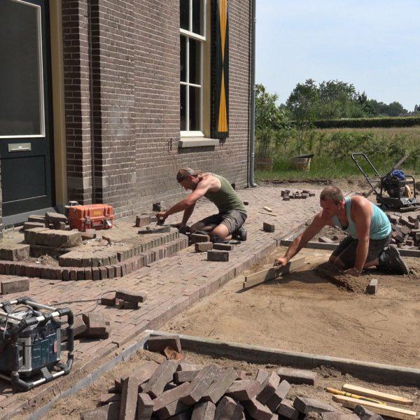 Wes en Kees leggen een terras voor het huis aan.